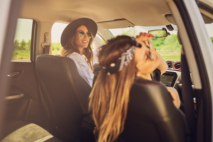 Two girls sitting in the car and looking through the window.